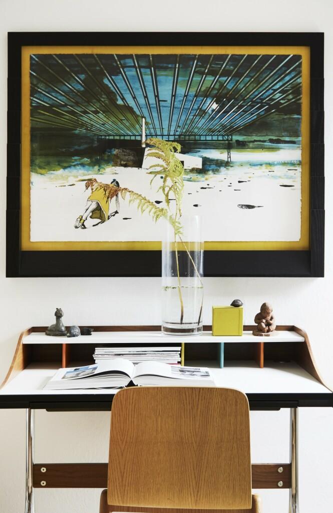 Kunstverket over arbeidspulten er av John Kørner, mens bordet «Swag Leg Desk» er designet av George Nelson i 1955. Tips! Du kan gjøre hjemmekontoret innbydende med et vakkert bilde over pulten, med noe grønt i en vase og med litt nips. FOTO: Nicoline Olsen