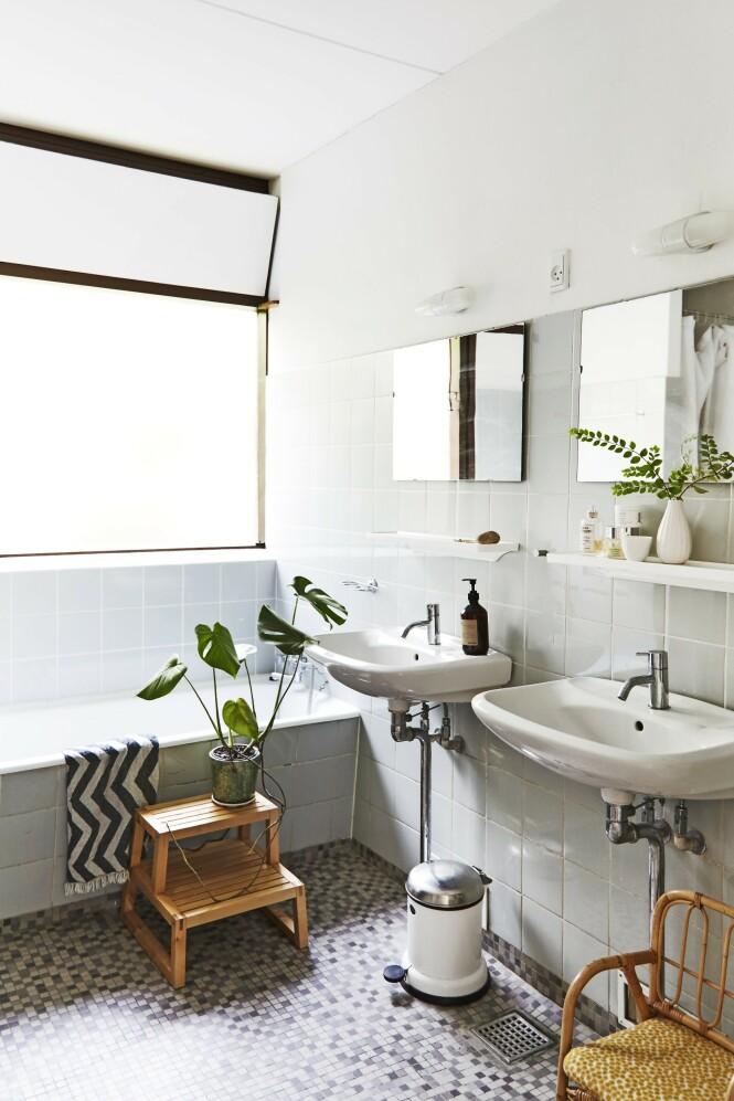 Badet er originalt og fungerer perfekt. En grønn plante og småmøbler i tre gir varme til de hvite vaskene, de sart lyseblå flisene og mosaikkgulvet. FOTO: Nicoline Olsen