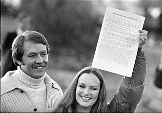 Patty Hearst holder opp papiret som slår fast at hun er benådet. Ved hennes side står forloveden Bernard Shaw. Foto: AP/NTB Scanpix