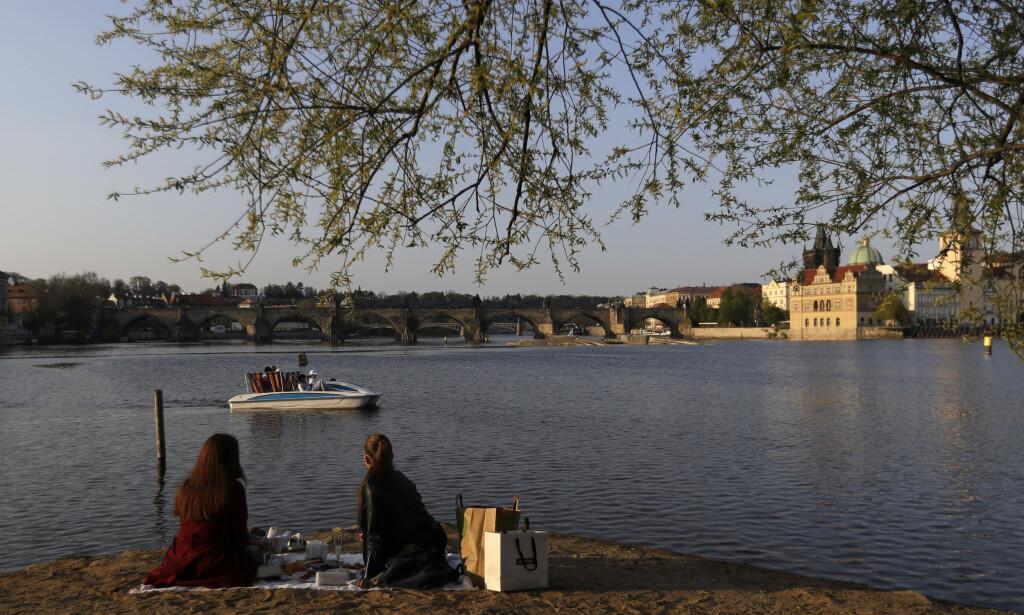 To kvinner nyter varmt vårvær ved Vltava-elva i Praha før helgen. Landet vil lette på noen av restriksjonene som er blitt innført for å bremse spredningen av koronaviruset. Foto: Petr David Josek /AP/NTB Scanpix
