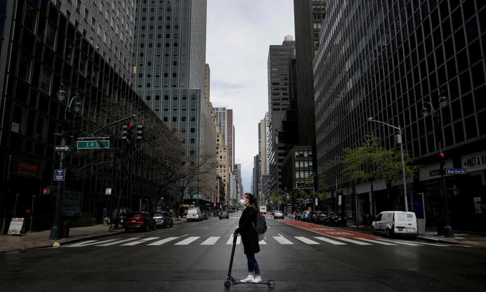 ENORM ØKNING: Antallet amerikanere som søker om arbeidsledighetstrygd er historisk høyt. Bildet viser en kvinne på sparkesykkel i en av de nærmest folketomme gatene i New York. Foto: Mike Segar / Reuters / NTB Scanpix