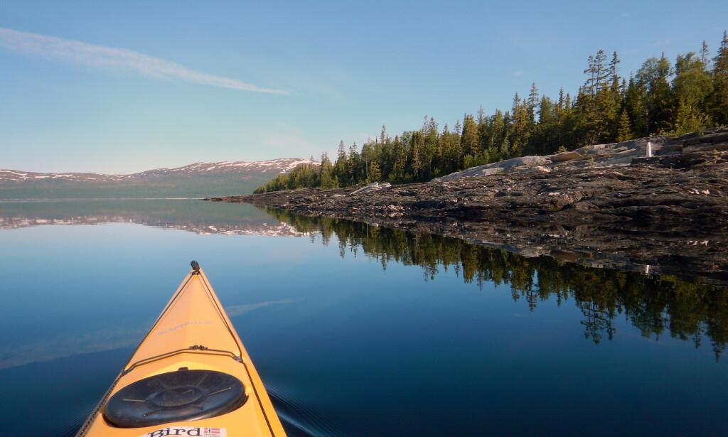 En padletur på Norges nest største innsjø, Røssvatnet, i sol og blikkstille vann er en god opplevelse (Foto: NAF).