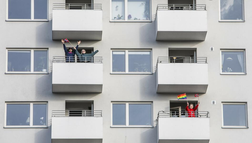 Beboere i Fossheim Borettslag ville vise samhold og dugnadsånd og gikk ut på balkongene sine for å klappe og flagge for de ansatte i samfunnskritiske jobber som holder Norge i gang under corona-pandemien. Foto: Ole Berg-Rusten/NTB scanpix