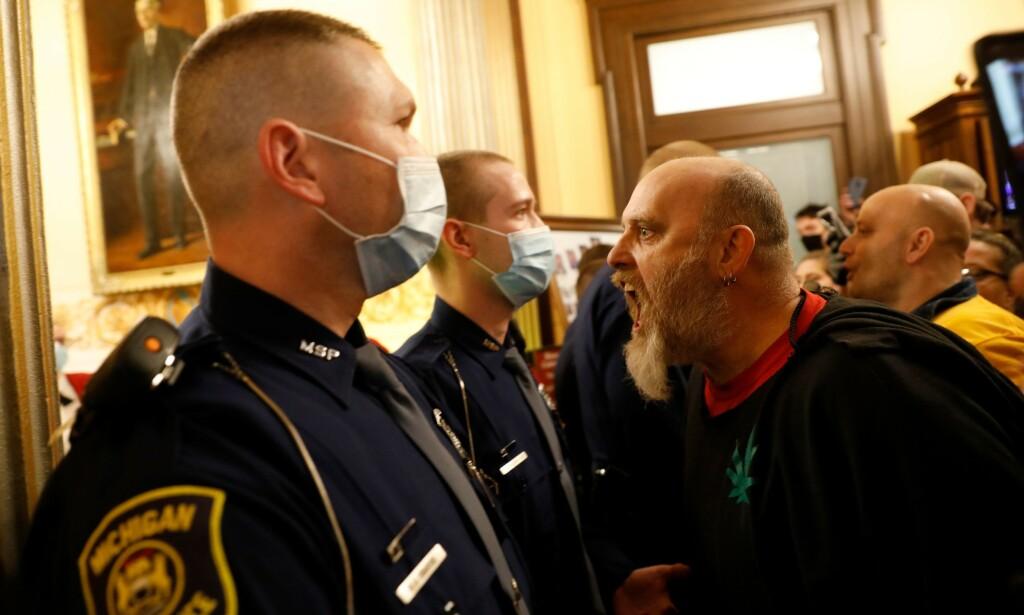SINTE: Delstatspolitiet i Michigan måtte stanse demonstranter som forsøkte å presse seg inn i delstatsforsamlingen. Foto: JEFF KOWALSKY / AFP)