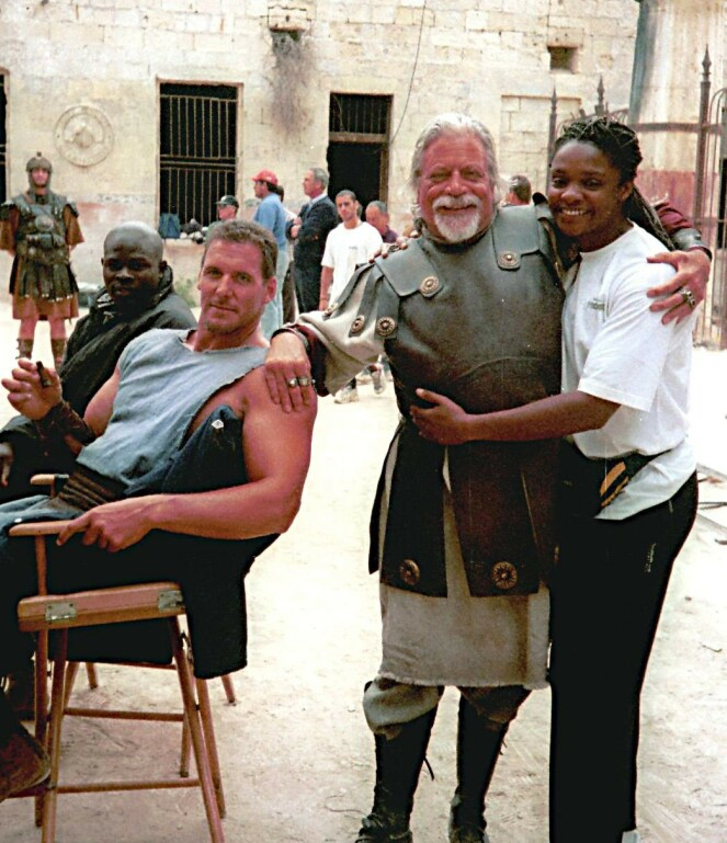 LYSTIG GJENG: Oliver Reed sammen med deler av staben, blant annet Pauline Richards, under innspillingen av «Gladiator» på Malta. FOTO: NTB Scanpix