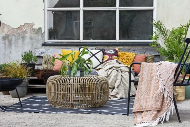 På terrassen har Fie reservert et område for avslapning og innredet med vakre, myke tekstiler. Tips! Rå mur og røft gulv står utrolig bra sammen med feminine og komfortable elementer som fargerike puter og pledd. FOTO: Mettemaje Skøtt og Camilla Skøtt