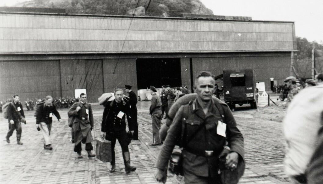 <strong>HJEMREISE:</strong> Tysk personell ved flyhangaren på Vestnes som trolig er blitt plukket ut for ytterligere forhør før forflytning og hjemsendelse til Tyskland etter frigjøringen i 1945. Foto: Arkivverket / SAS