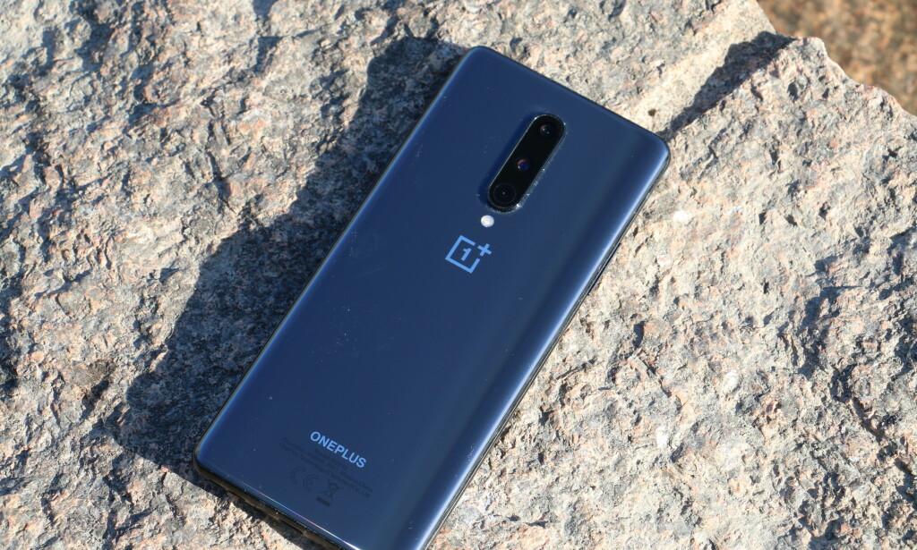 OnePlus 8 har en bakside i glass, men det er kun Pro-modellen som kan lades trådløs. Legg merke til støvsamleren rundt kamerahakket. Foto: Martin Kynningsrud Størbu