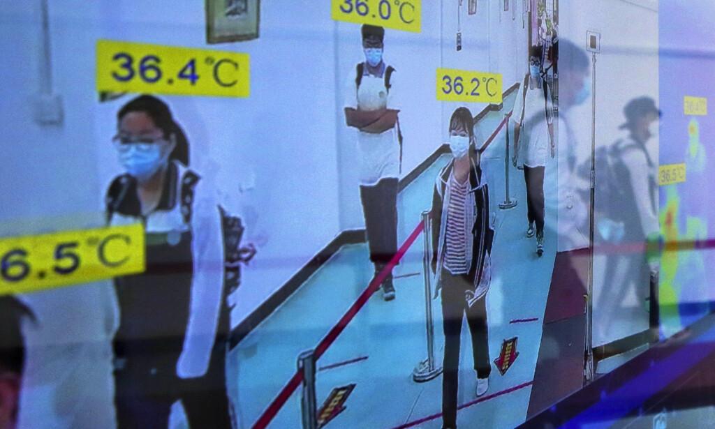 SMITTEVERNTILTAK: Kina har fortsatt strenge smitteverntiltak. Her passerer folk gjennom en temperaturmåler ved et handlestrøk i Beijing. Foto: Mark Schiefelbein / AP / NTB scanpix