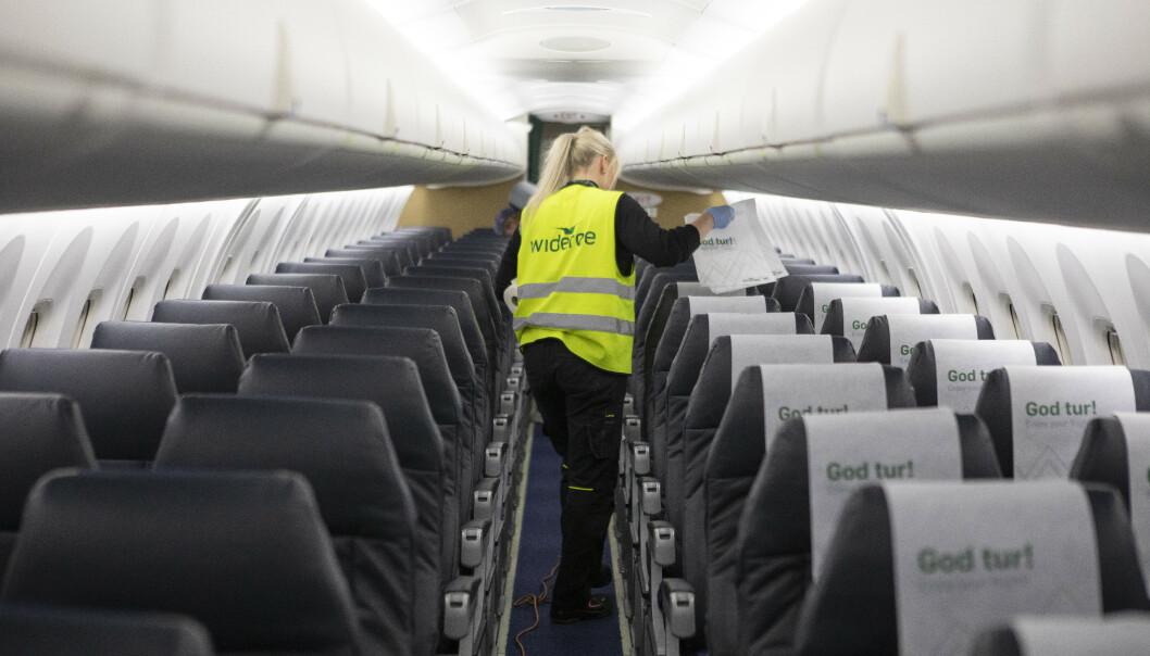 <strong>AVVENTER:</strong> Det bir foreløpig ikke påkrevd bruk av munnbind på Widerøes flyvninger. Her fra renhold og desinfeksjon av ett av deres fly. Foto: NTB Scanpix