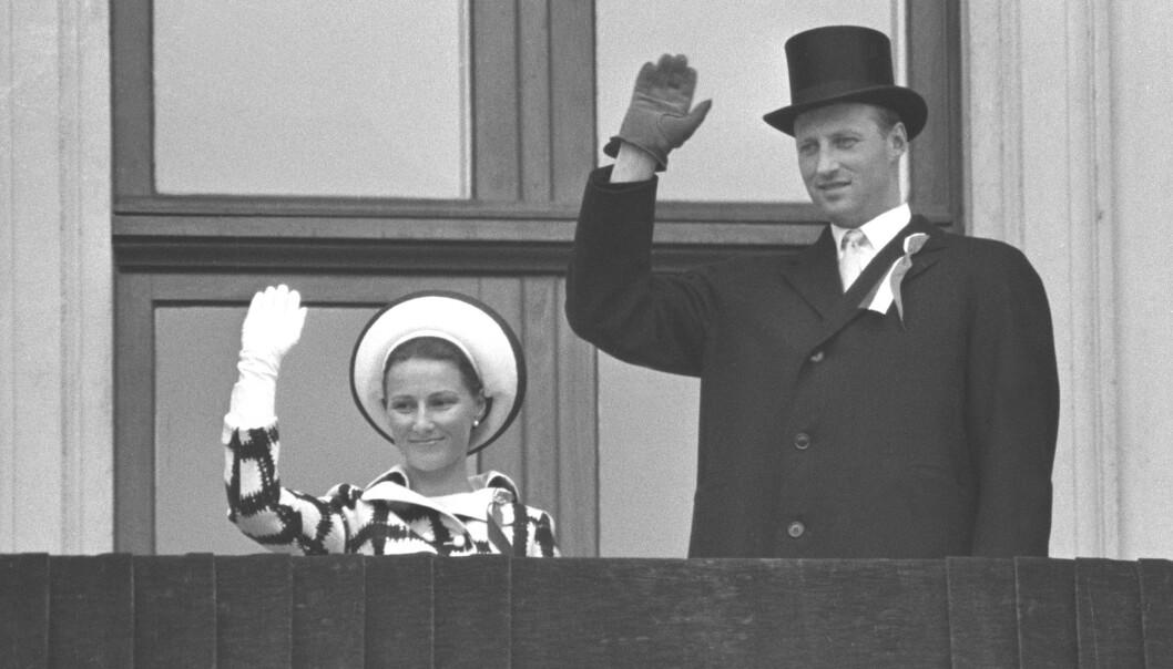 <strong>UTEN KONGEN:</strong> Kronprins Harald og kronprinsesse Sonja vinker til barnetoget på Slottsbalkongen uten kong Olav i 1970. Kongen var syk og kunne ikke være til stede. Foto: NTB Scanpix