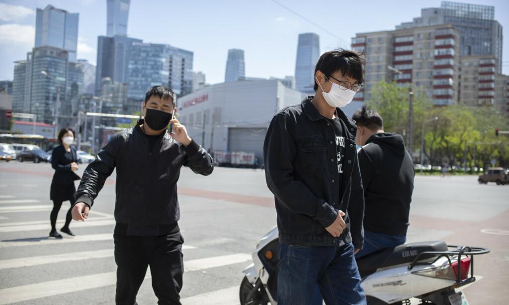 Folk med munnbind i den kinesiske hovedstaden Beijing. Forskere ved byens universitet mener å kunne stoppe koronapandemien uten at man må vente på en vaksine. Foto: Mark Schiefelbein / AP / NTB scanpix