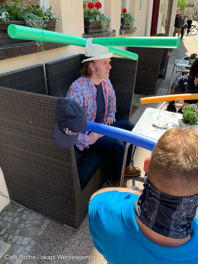 PØLSETREFF: På Café Rothe praktiserte man sosial distansering ved hjelp av spesialdesignede hatter på gjenåpningen. Foto: Café Rothe Schwerin/Jacqueline Rothe