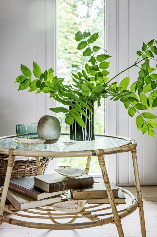 Skap deilig sommerstemning med lyse, gamle bambus- og rattanmøbler og grønne greiner i vaser. Tips! Dropp innkjøpte blomsterbuketter. Ute er det fullt av grønne greiner og markblomster som er enda vakrere. FOTO: Christina Kayser O.