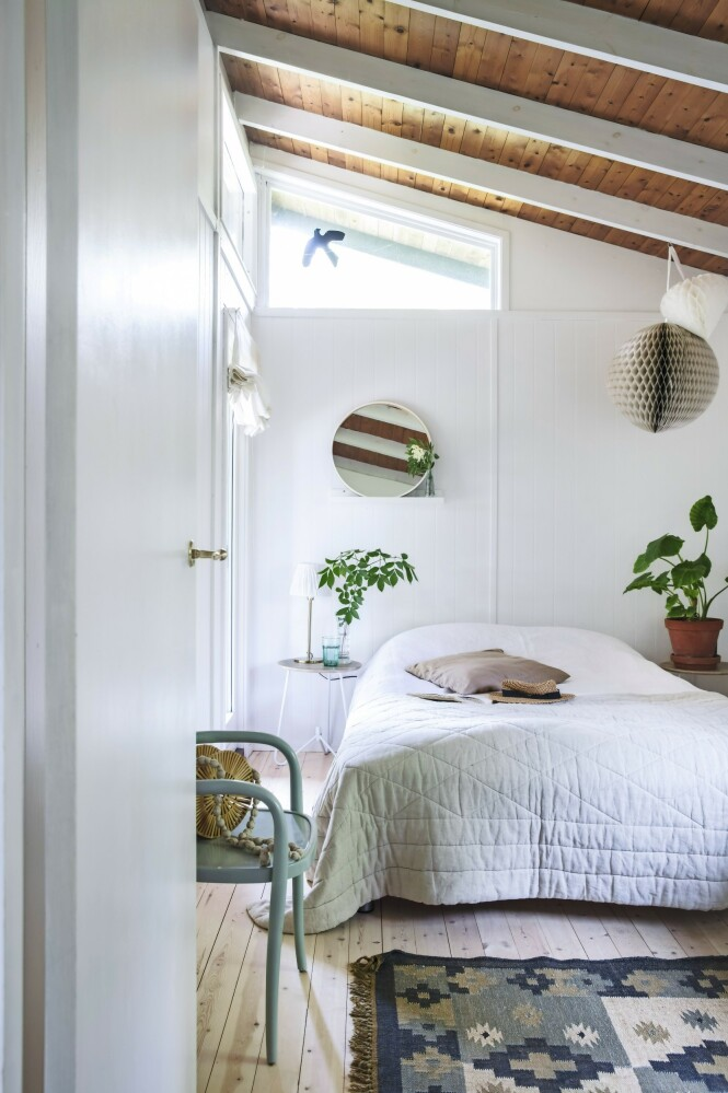Selv det lille soveværelset er lyst og luftig fordi det er skråtak med vinduer høyt oppe. Sengeteppet er fra Tine K Home, og kelimteppet er kjøpt i en teppebutikk for mange år siden. Stolen er et loppefunn. Tips! Stilen med hvitmalte bjelker, umalte tretak og hvite vegger er videreført i alle rom. Slik virker det lille huset harmonisk og større enn det er. FOTO: Christina Kayser O.
