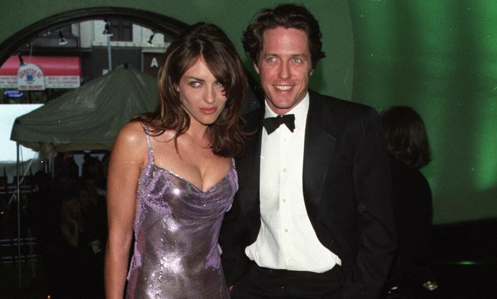 IKONISK: Elizabeth Hurley hadde på seg denne Versace-kjolen i 1999, da hun og hennes daværende kjæreste Hugh Grant dukket opp på CFDA Awards i New York. Nå har hun funnet frem kjolen igjen - 21 år senere. Hurley og Grant gikk for øvrig hver til sitt det påfølgende året. Foto: NTB Scanpix