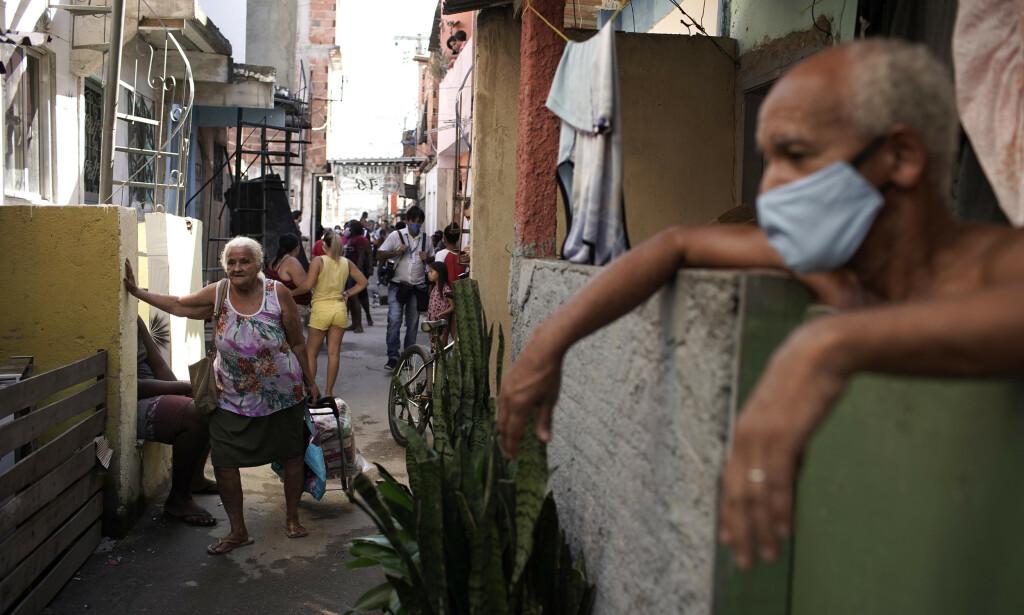 HENTER FORYNINGER: En eldre kvinne henter matforsyninger fra en frivillig organisasjon i Mandela-favelaen i Rio de Janeiro i slutten av april. Foto: Silvia Izquierdo/AP