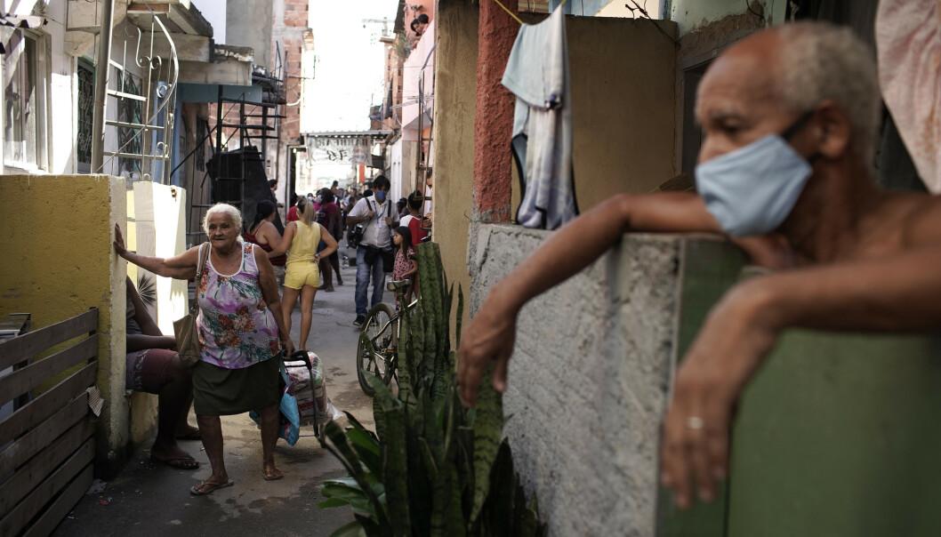 <strong>HENTER FORYNINGER:</strong> En eldre kvinne henter matforsyninger fra en frivillig organisasjon i Mandela-favelaen i Rio de Janeiro i slutten av april. Foto: Silvia Izquierdo/AP