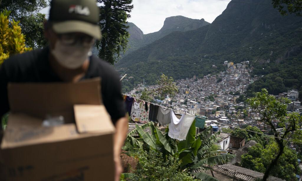 BISTÅR: En frivillig bistår med såpe og håndesinfeksjonsmiddel til inbyggerne i Rochina-favelaen i Rio de Janeiro. Foto: Leo Correa/ AP