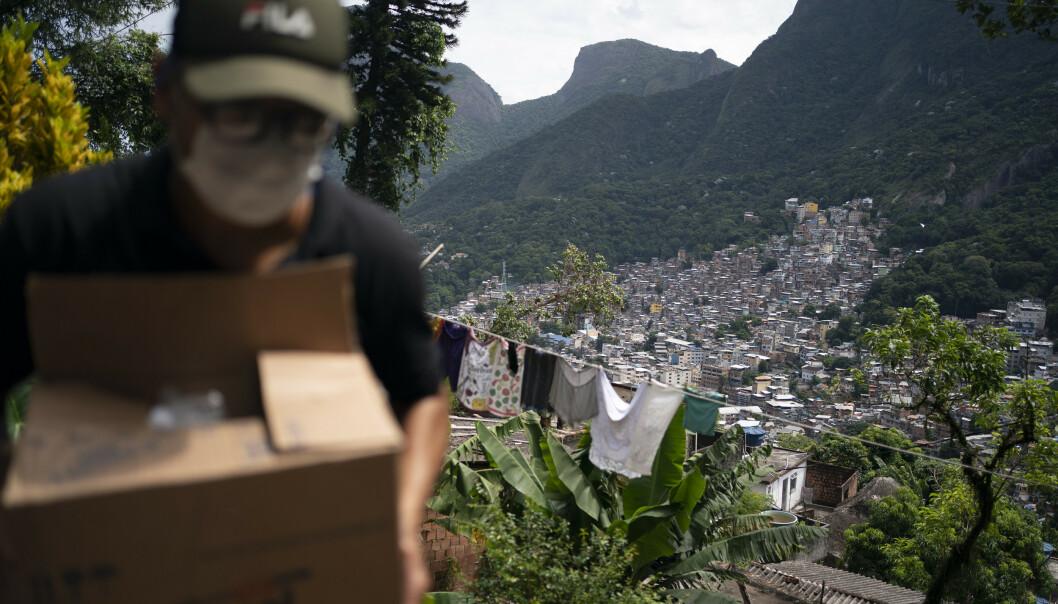 <strong>BISTÅR:</strong> En frivillig bistår med såpe og håndesinfeksjonsmiddel til inbyggerne i Rochina-favelaen i Rio de Janeiro. Foto: Leo Correa/ AP