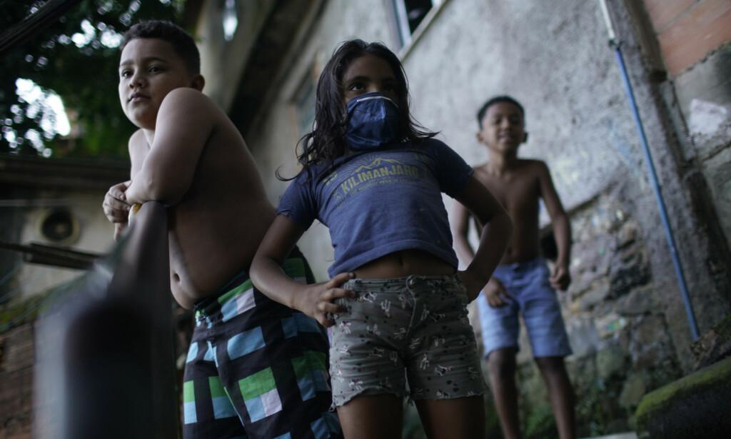 FØLGER MED: Lokale barn følger med på desinfiseringen av gatene i Santa Marta-favelaen. Foto: AFP/ NTB scanpix