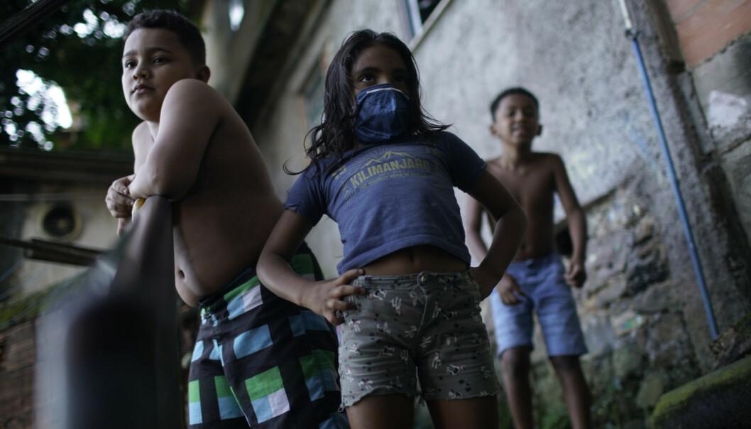 <strong>FØLGER MED:</strong> Lokale barn følger med på desinfiseringen av gatene i Santa Marta-favelaen. Foto: AFP/ NTB scanpix