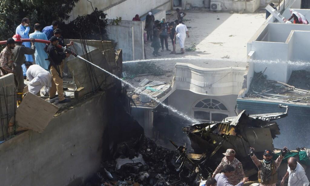 KRASJSTEDET: Redningsmannskaper spyler vann på det som skal være restene av et passasjerfly fra Pakistan International Airlines, etter at det styrtet i et boligområde utenfor byen Karachi fredag. Foto: Asif HASSAN / AFP / NTB scanpix