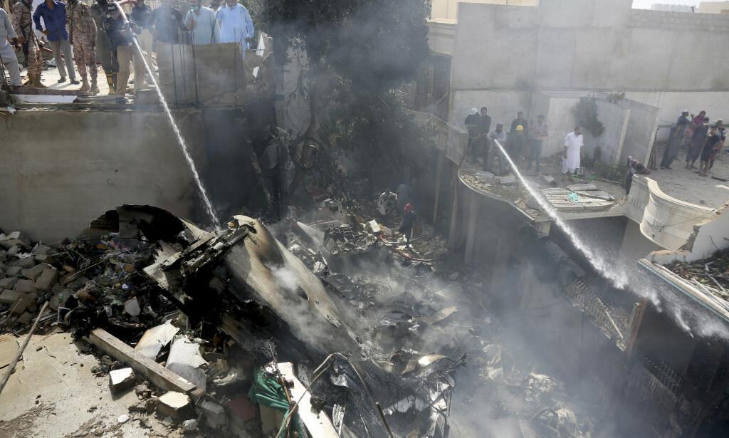 107 OMKOM: Brannvesenet forsøker å slukket brannen i det som skal være vrakrester fra passasjerflyet som styrtet i Pakistan fredag. Foto: AP Photo / Fareed Khan / NTB scanpix