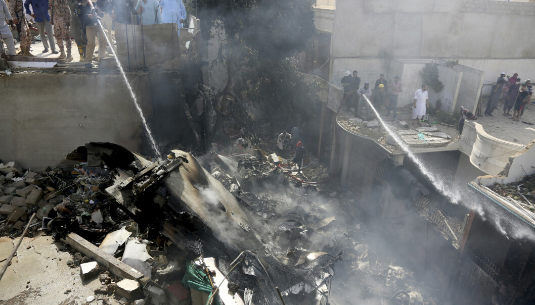 <strong>107 OMKOM:</strong> Brannvesenet forsøker å slukket brannen i det som skal være vrakrester fra passasjerflyet som styrtet i Pakistan fredag. Foto: AP Photo / Fareed Khan / NTB scanpix