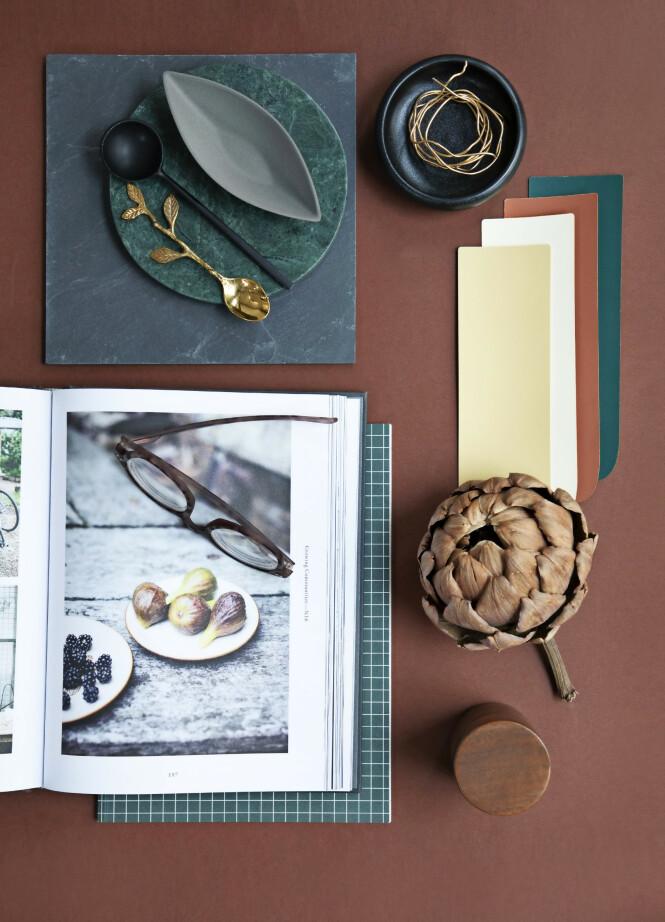 Skiferplate, grønn marmorbrikke, svart skål, svart skje og messingskje (alt fra Notre Dame). Avlang, liten skål/saltkar (Ditte Fischer). Rutete notatbok (Kartotek). Bakgrunnen er malt i fargen 3397, og fargeprøvene er Lys gul 1322 og Grønn 3508 fra Flügger. FOTO: Pernille Enoch