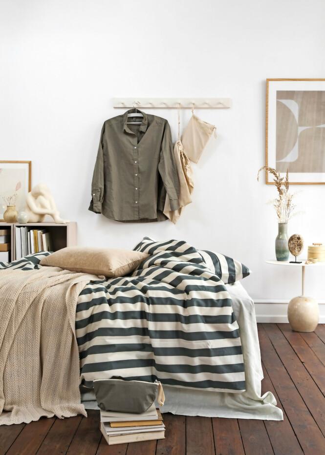 Bokkasser (Trævarefabrikernes Udsalg). Kassene er malt i fargen 3372 fra Flügger. Lite bilde i ramme og stort bilde i ramme (begge fra The Poster Club). Keramikkule (Søstrene Grene). Knaggrekke (Trævarefabrikernes Udsalg). Knaggene er malt i fargen 4371 fra Flügger. Stoffposer med sengetøy, skjorte, sengetøy, pute, pledd og toalettveske (alt fra Aiayu). Figur og vase på bokkassene er funnet brukt. FOTO: Pernille Enoch
