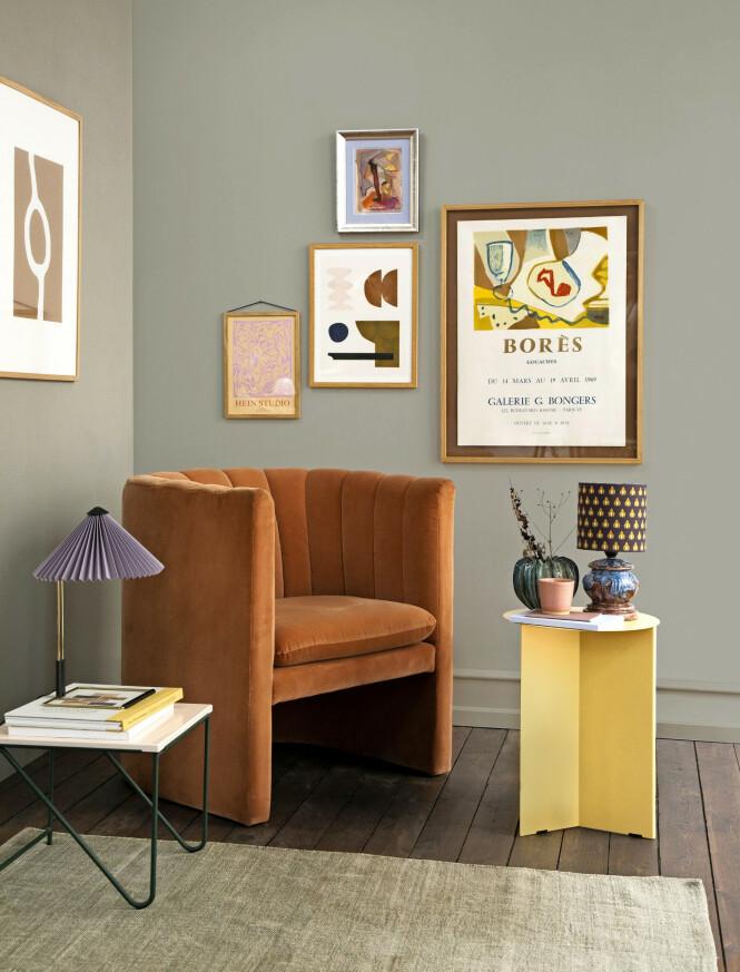 Stort bilde med sirkel og lite bilde med grafiske mønstre (begge fra The Poster Club). Borèskunstplakat og bilde i sølvramme (begge fra Bendtsens). Rosa bilde (Stilleben). Gult bord og lampe med liten skjerm (begge fra Hay). Velurstol (&tradition), bord med steinplate (Please Wait to be Seated). Krus (Stilleben), vase (Broste Copenhagen). Gulvteppe (Jysk). Vintagelampe (Bendtesen). Veggen er malt i fargen 5336 fra Flügger. FOTO: Pernille Enoch