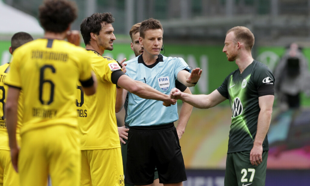Referee Daniel Siebert gestures to Wolfsburg's Maximilian Arnold, right, bumping elbows with Dortmund's Mats Hummels during the German Bundesliga soccer match between VfL Wolfsburg and Borussia Dortmund in Wolfsburg, Germany, Saturday, May 23, 2020. The German Bundesliga is the world's first major soccer league to resume after a two-month suspension because of the coronavirus pandemic. (AP Photo/Michael Sohn, Pool)