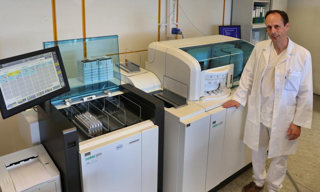 STOLT: Overlege Andreas Lind og analysemaskinen Roche Cobas Pro. Sammen kan de forhåpentligvis gi svaret på noen av coronavirusets største mysterier. Foto: Anders bayer / OUS