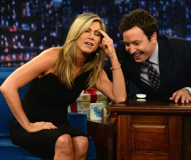 LEGGER SEG FLAT: Talkshowstjernen Jimmy Fallon har hatt enorm suksess i mange år. Nå legger han seg imidlertid flat etter en gammel blemme. Her fra sitt eget show med Jennifer Aniston som gjest. Foto: NTB Scanpix