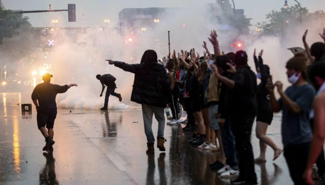 <strong>TÅREGASS:</strong> Politiet tok blant annet i bruk tåregass under demonstrasjonen utenfor politistasjonen i Minneapolis tirsdag. Foto: AFP