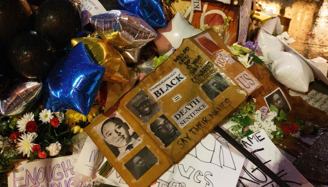 <strong>MINNES FLOYD:</strong> Store mengder blomster og plakater er lakt på stedet George Floyd ble tatt av politiet mandag. Foto: AFP