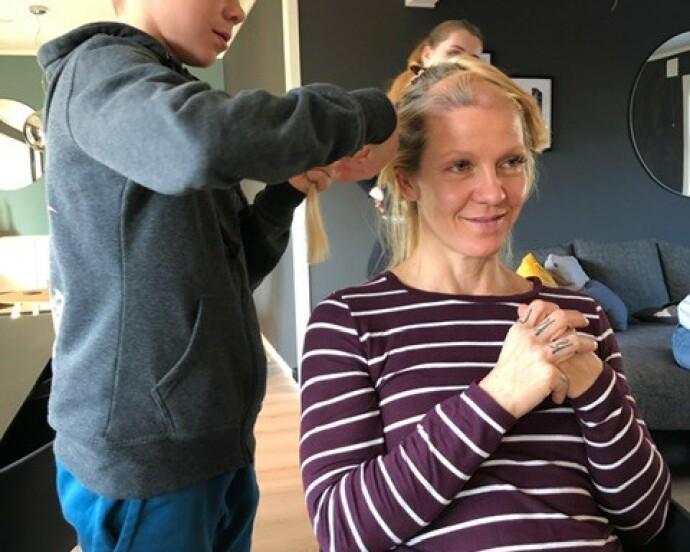 <strong>BARNA HJALP:</strong> Da håret begynte å falle av som følge av stråling og cellegift, bestemte Monica seg for å barbere hodet. Her får hun hjelp av sønnen Kristoffer. FOTO: Privat