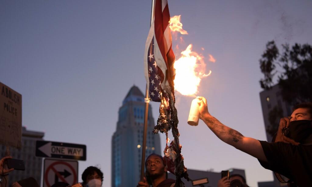 BRANT FLAGG: Det har vært heftige protester i gatene etter at George Floyd mistet livet i politivold på mandag, som her i Los Angeles. Foto: NTB Scanpix/Agustin Paullier/ AFP