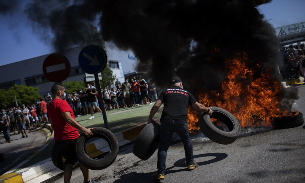 DEMONSTRERTE: Brennende bildekk og maskekledde demonstranter var det som møtte ledelsen ved Nissans fabrikk i Barcelona torsdag. Foto: Emilio Morenatti / AP / NTB Scanpix