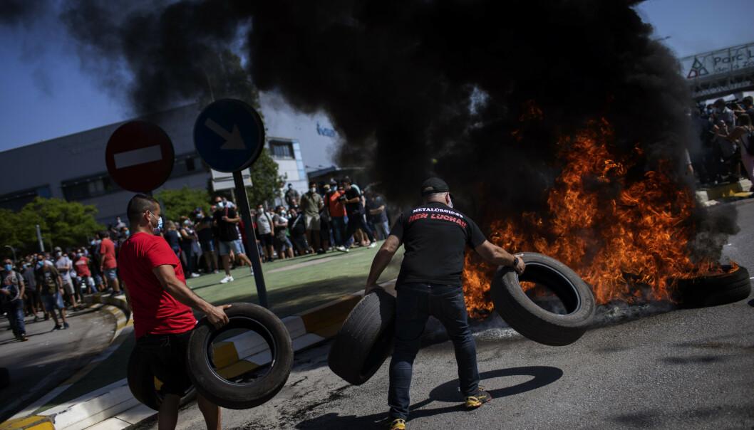 <strong>DEMONSTRERTE:</strong> Brennende bildekk og maskekledde demonstranter var det som møtte ledelsen ved Nissans fabrikk i Barcelona torsdag. Foto: Emilio Morenatti / AP / NTB Scanpix