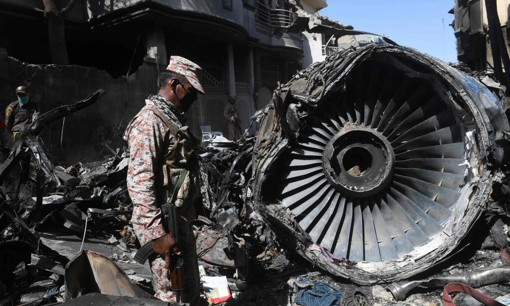 TOK FYR: Flyet tok fyr etter å ha styrtet i et boligområde utenfor Karachi. Vrakrestene ligger strødd i boligområdet, og har medført store skader. Foto: Asif HASSAN / AFP / NTB scanpix
