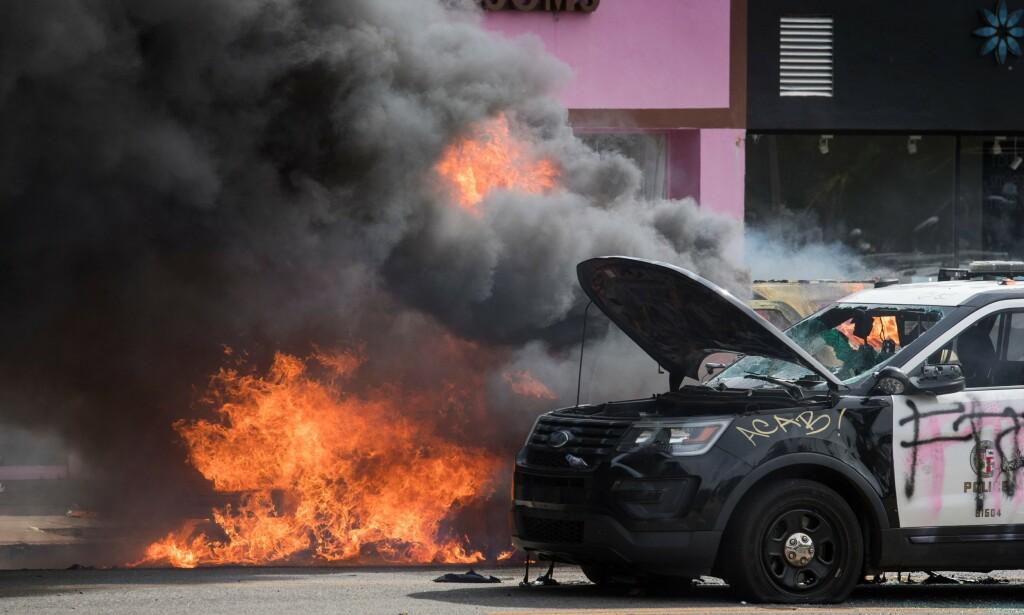 RAMPONERT: Politibiler ble fullstendig ødelagt og satt i brann under demonstrasjoner i Los Angeles. Foto: Mark RALSTON / AFP
