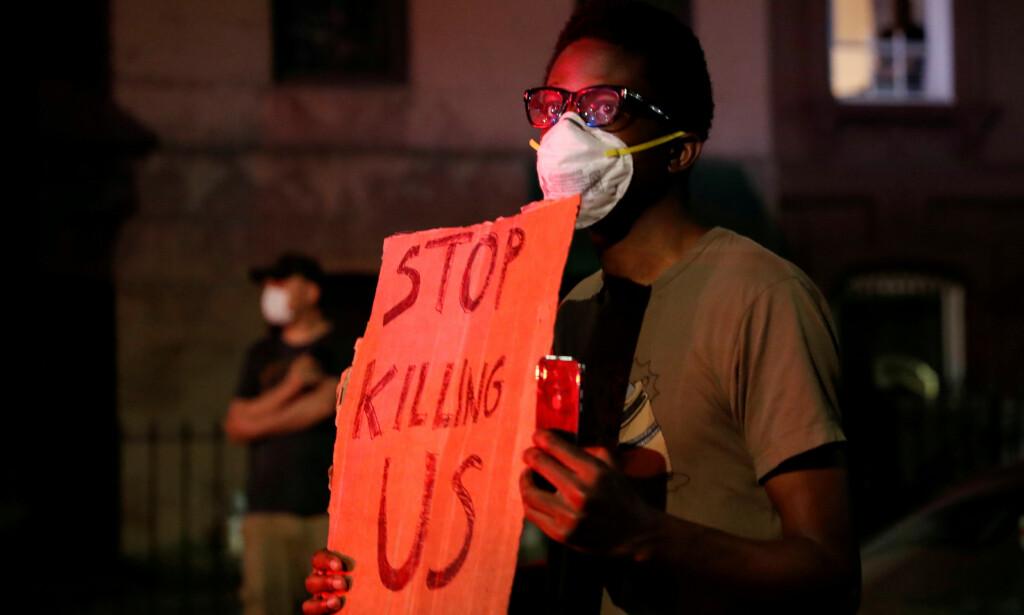 «STOP KILLING US»: En afroamerikansk mann holder opp et skilt med påskriften «STOP KILLING US» under en demonstrasjon i Brooklyn i New York fredag. Flere mørkhudede sier de frykter for sine liv i USA. Foto: REUTERS / Shannon Stapleton / NTB scanpix