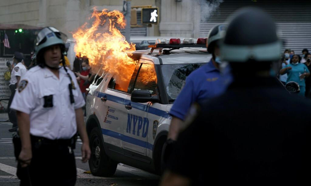 ANGRIPER POLITIET: En politibil i New York ble satt i flammer under voldsomme protester lørdag. Foto: REUTERS / Eduardo Munoz / NTB scanpix