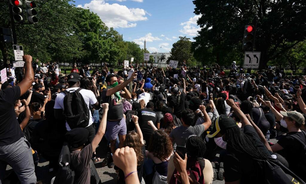 KNELER: Søndag ettermiddag lokal tid har en stor mengde demonstranter samlet seg utsiden av Det hvite hus på nytt. På bildet kan man se at mange av dem kneler. Foto: Mandel Ngan / AFP