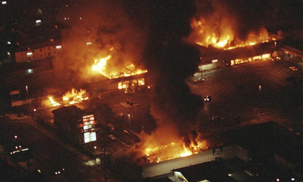 I FLAMMER: Los Angeles tok fyr, bokstavlig talt, i seks døgn fra 29. april 1992. Da ble fire politimenn frikjent for vold under under pågripelsen av Rodney King i mars året før. Her er et shoppingsenter satt i brann. Foto: AP/NTB Scanpix.