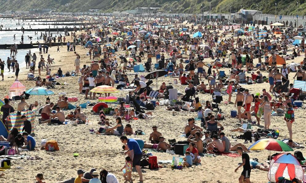 FORTVILER: Et enormt antall mennesker flokket til denne stranda i Bournemouth sør i England 25. mai, etter at myndighetene lettet på noen av de strenge corona-restriksjonene. Nå fortviler britiske reiselivsgiganter over nye regler. Foto: Glyn Kirk / AFP / NTB Scanpix