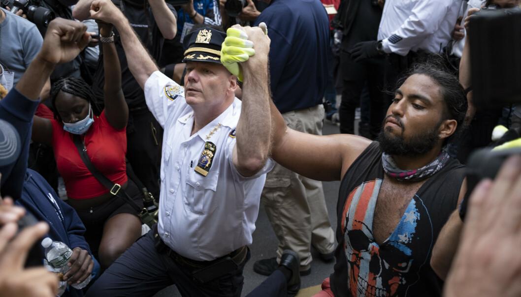 KNELTE: Natt til tirsdag norsk tid valgte politimannen Terence Monahan å knele sammen med demonstrantene i New York. Foto: Ap / Craig Ruttle