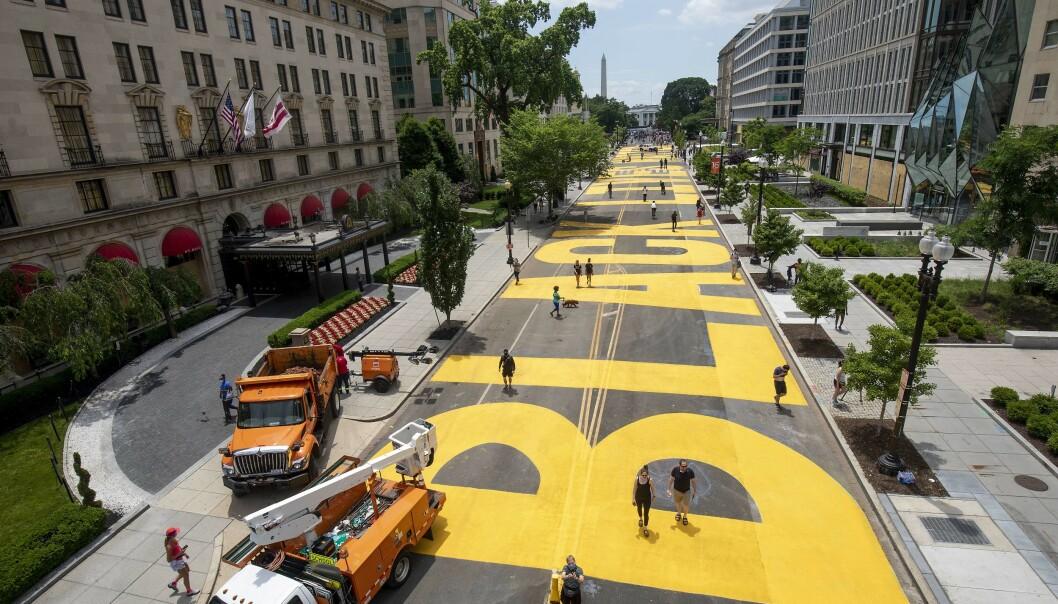 MALTE: Fredag var lokale kunstenere travelt opptatt med å male gata i de enorme gule bokstavene. FOTO: AFP